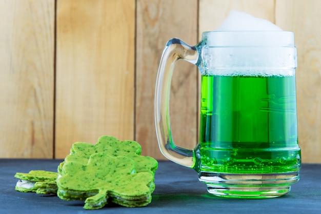 聖パトリックの日のシャムロックの形でショールと緑のビール Premium写真