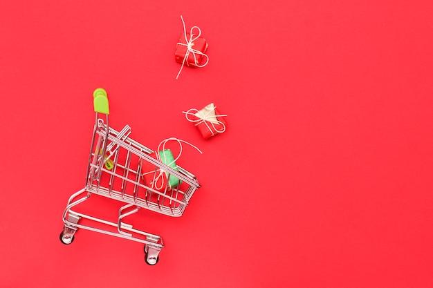 ギフト、トップビューで赤の背景にショッピングトロリー。コピースペース。ビジネス、セールスコンセプト Premium写真