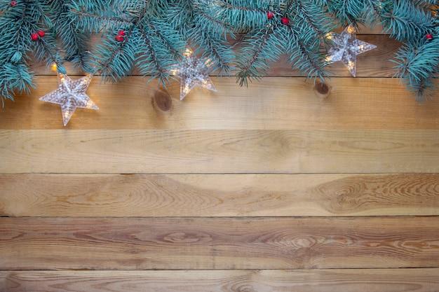 クリスマスのモミの木と木製の背景にガーランド。コピースペース Premium写真