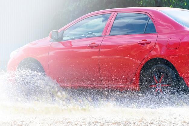 赤い車は大きな水たまりに乗っています。水のしぶき。 Premium写真