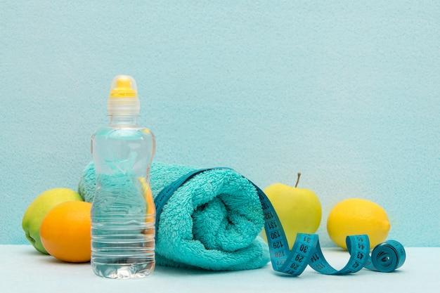 果物、タオル、水のボトルの背景に測定テープ。 Premium写真