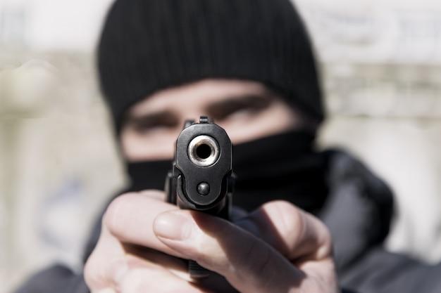 彼の手に銃を持つマスクの若い男。引き締まった Premium写真