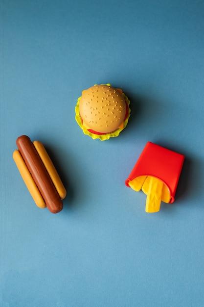 プラスチックのハンバーガー、サラダ、トマト、フライドポテトと青色の背景にホットドッグ Premium写真