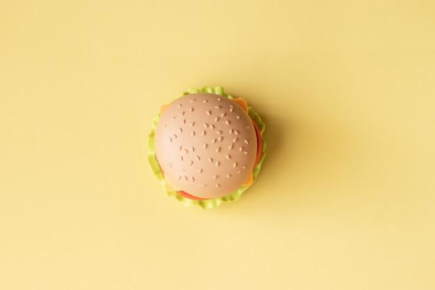 プラスチックのハンバーガー、サラダ、トマト、黄色の背景に Premium写真