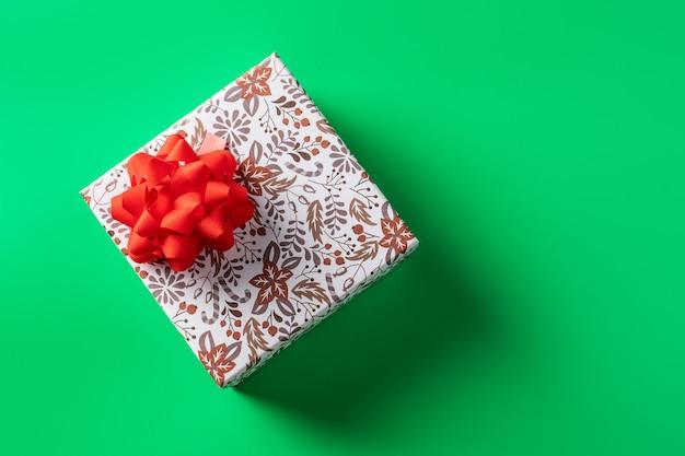 休日のための緑の背景に赤の弓とギフトボックス。コピースペース Premium写真