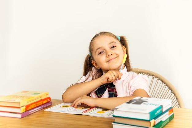 白い背景の上のテーブルで勉強している女の子 Premium写真