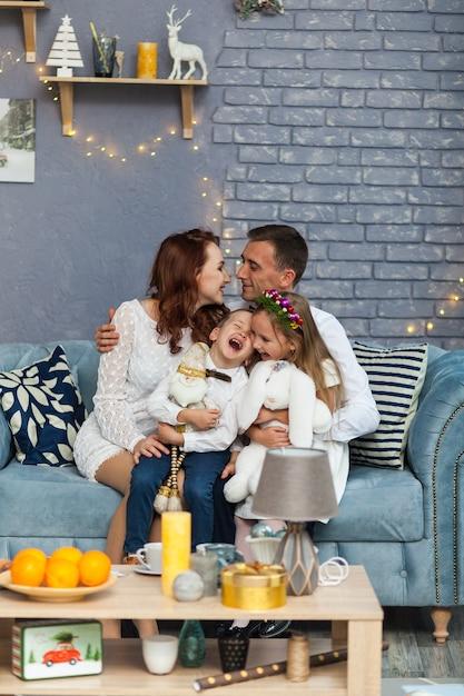 カメラ目線のクリスマスプレゼントを持って幸せな家族 Premium写真