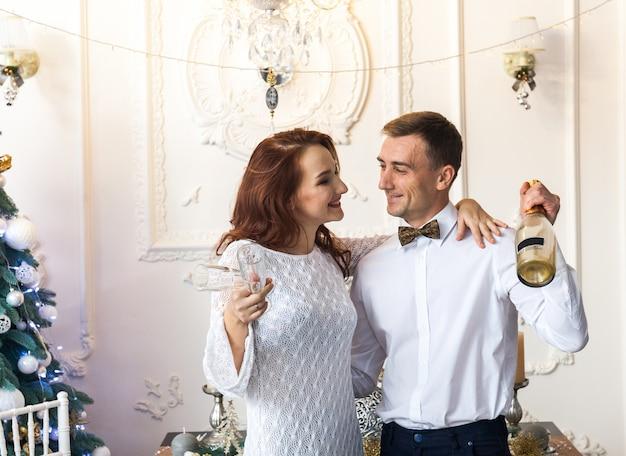 自宅でクリスマスを祝う美しい若いカップル Premium写真