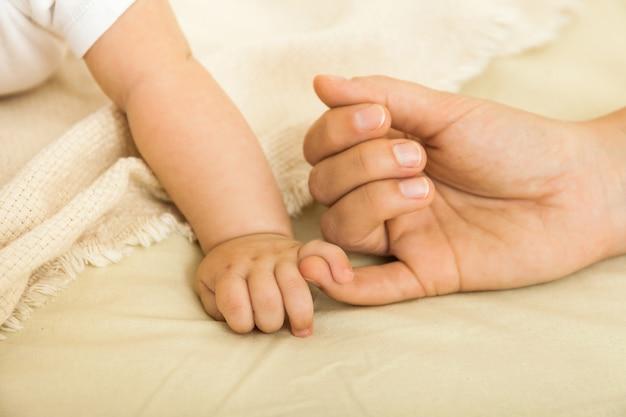 赤ちゃんと母親の手のクローズアップ。家族の概念 Premium写真