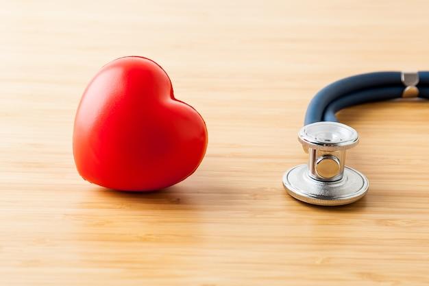 医療と医療のコンセプト。木製のテーブルに聴診器と赤いハート。 Premium写真