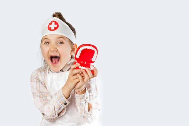 歯科医のツールで幸せな笑顔の女の赤ちゃん Premium写真