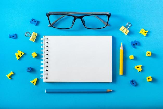 モーションキャプチャメモ帳。メガネと青色の背景に木製の手紙。先生の日の概念と学校に戻る。 Premium写真