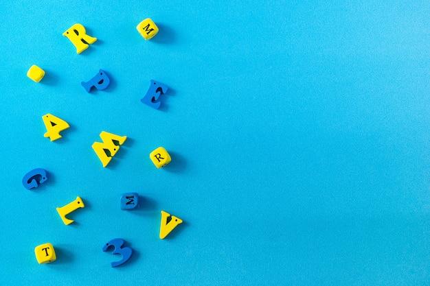 青色の背景に学用品。学校と教師の日の概念。コピースペースを持つテーブルの上の木製の手紙。 Premium写真