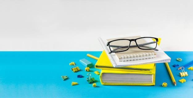 Учитель очки, книги и деревянные буквы на синем столе. школа и учитель день концепция. копировать пространство Premium Фотографии