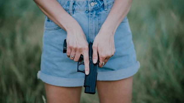 デニムのショートパンツとフィールドでポーズをとって彼の手で銃を持つ少女。 Premium写真
