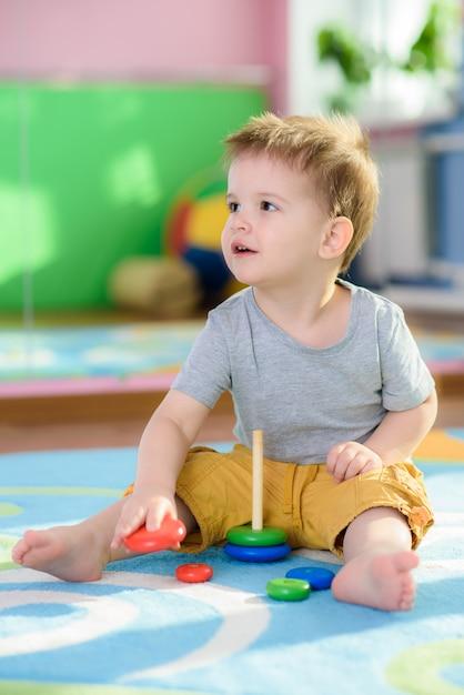 小さな子供は床に座ってピライムダを収集します Premium写真