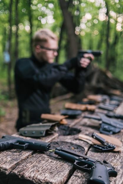 Парень в лесу проверяет свое оружие для спортивной стрельбы Premium Фотографии
