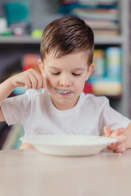 美しい少年は牛乳を食べる。自宅の台所のテーブルに座って朝食を持っているかわいい赤ちゃん。 Premium写真