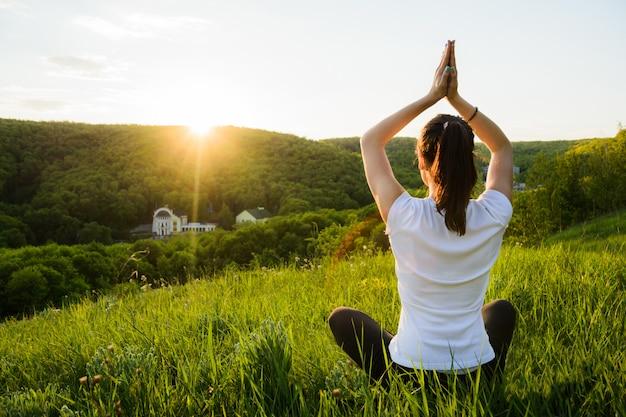 Девушка занимается медитацией на природе Premium Фотографии