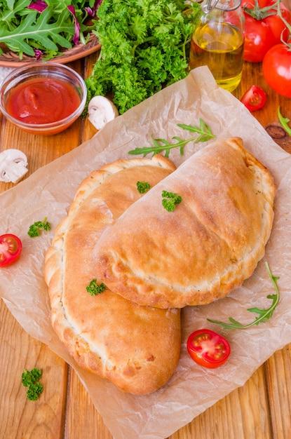 トマトソース、チーズ、ハーブ、マッシュルーム、ソーセージのピザカルゾーネ。イタリア料理。 Premium写真