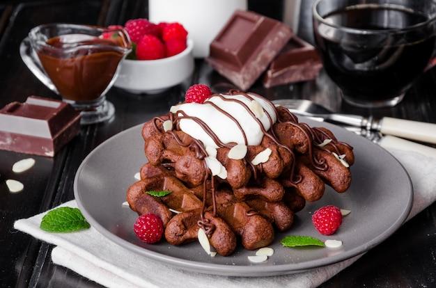 チョコレート、ワッフル、グレーズ、ホイップクリーム、アーモンドの花びら、ラズベリー、ダークウッド Premium写真
