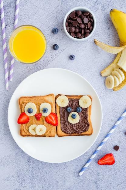 子供のための健康的な変な顔のサンドイッチ。アニマルフェイストースト Premium写真