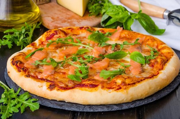 暗い石の上にトマトソース、スモークサーモン、新鮮なルッコラを添えた伝統的なイタリアのピザ。 Premium写真