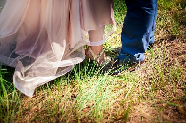緑の芝生で新郎新婦の足 Premium写真