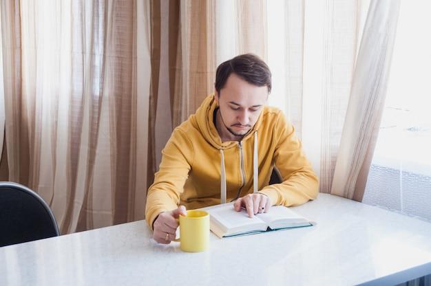 テーブルと読み取りで窓の近くに座っている男 Premium写真