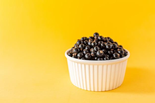 黄色の小さな白いカップに熟した黒スグリまたはブルーベリー Premium写真