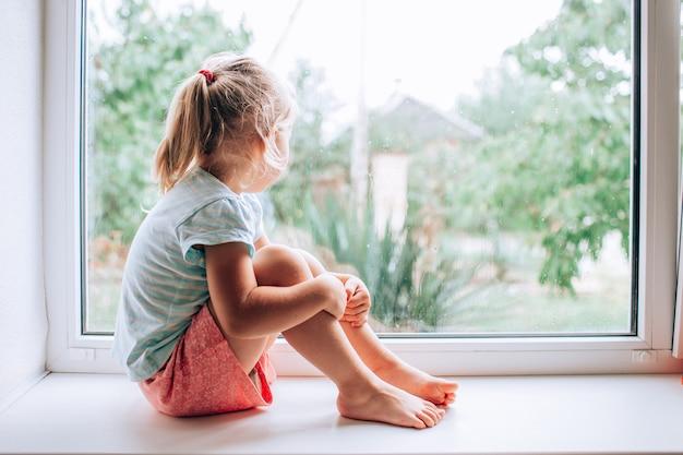 Великолепная маленькая блондинка смотрит в окно в мокрый, холодный дождливый день Premium Фотографии