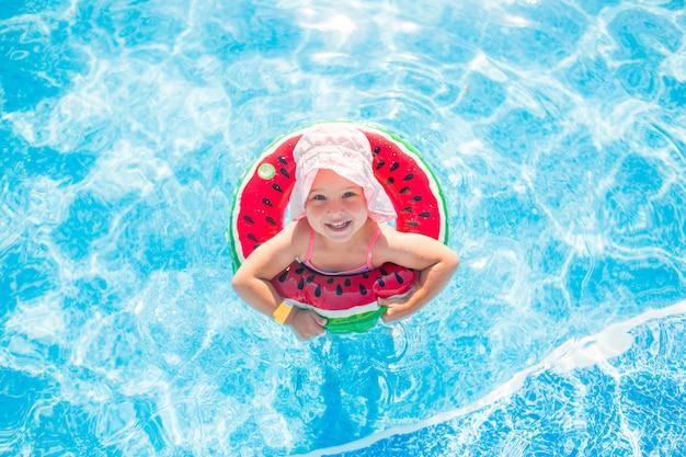 水泳、夏休み - テキストの救命浮輪 - スイカスペースと青い水で遊ぶピンクの帽子で素敵な微笑の女の子。 Premium写真
