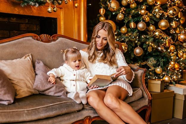 母と娘はクリスマスイブに暖炉のそばで本を読んでいます。装飾されたリビングルームには、木、暖炉、ギフトがあります。両親と子供のための家での冬の夜。 Premium写真