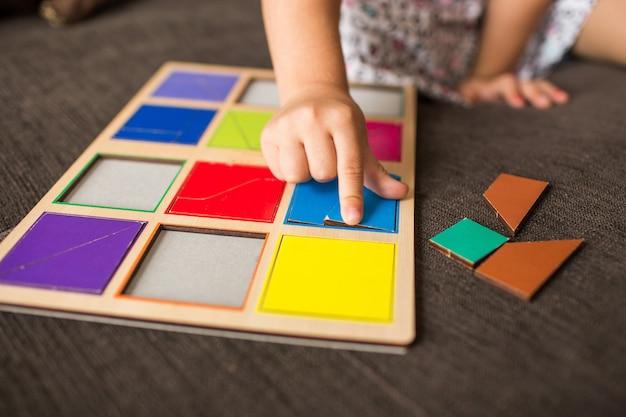ソファの上の木製モザイクで遊ぶ少女の手。教育的なゲーム。モンテッソーリ幼稚園の早期開発 Premium写真
