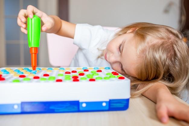おもちゃのドライバーと多色のネジで遊んで自宅のテーブルに座って幸せなかわいい金髪少女。早期教育。 Premium写真