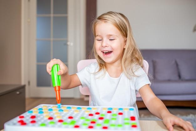 おもちゃのドライバーと晴れやかな笑顔で多色のネジで遊んで自宅のテーブルに座って幸せなかわいい金髪少女。早期教育。 Premium写真