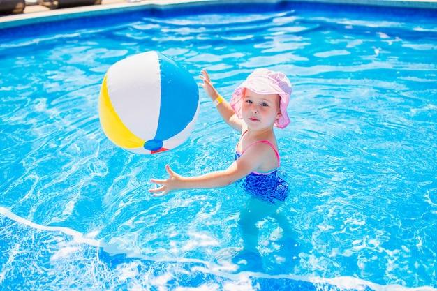 Плавание, летние каникулы - милая улыбающаяся девушка в розовой шляпе и синем купальнике играет в голубой воде с надувным разноцветным шариком в бассейне Premium Фотографии