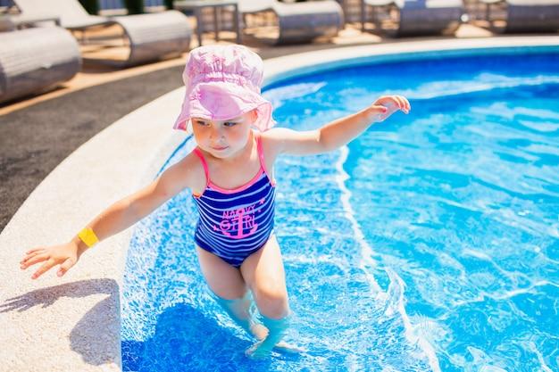 Плавание, летние каникулы - милые улыбающиеся девушки в розовой шляпе и синий купальник, играя в голубой воде в бассейне. Premium Фотографии