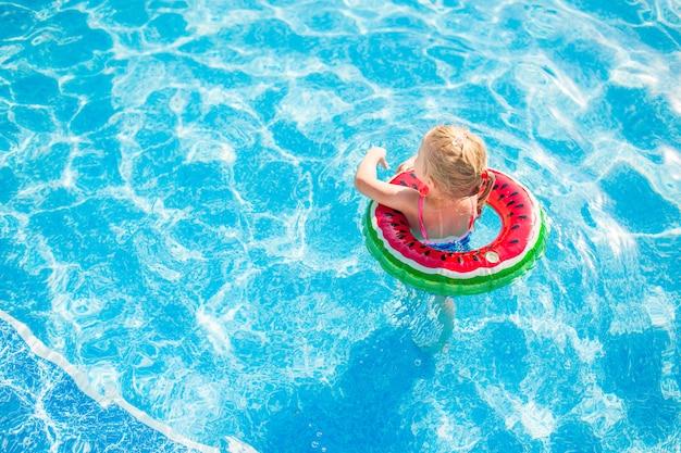 水泳、夏休み-救命浮輪スイカと青い水で遊ぶ素敵な笑顔の女の子。 Premium写真