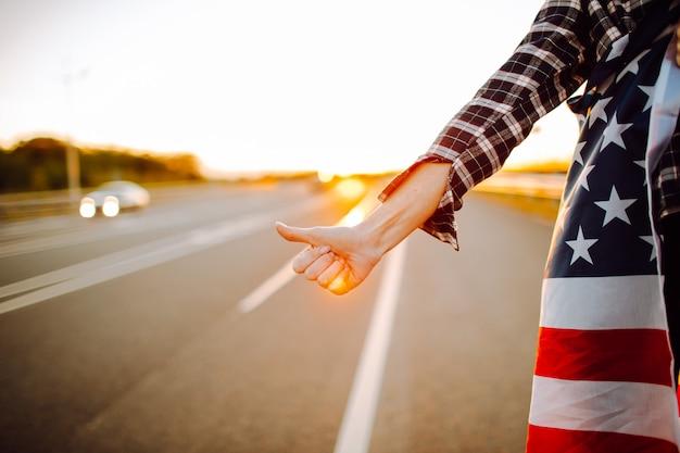 Молодой женский турист с американским флагом путешествовать автостопом по пустынной дороге Premium Фотографии