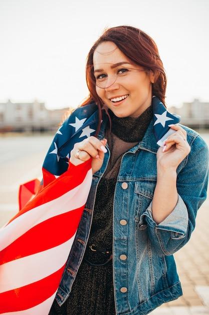 日差しの中でアメリカの国旗に包まれた若いかなり赤い髪の女性。 Premium写真