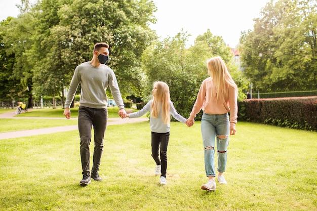Члены семьи гуляют по парку в тканевых лицевых масках. Premium Фотографии