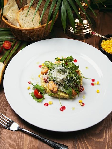 新鮮な野菜とチキンのシーザーサラダ。木のテーブル、おいしいサラダの白いプレートのサラダ 無料写真