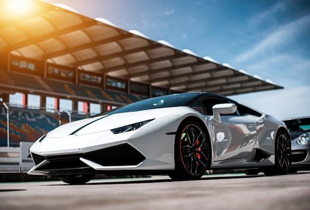 レーストレース、フロントサイドビューに立っている白い高級スポーツセダン車。 無料写真