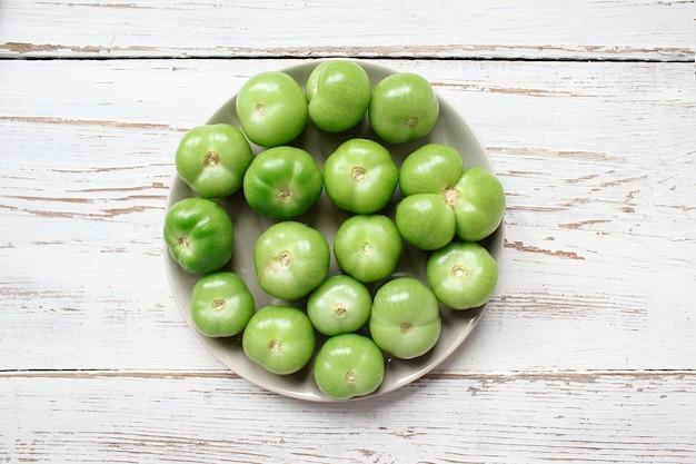 Зеленые помидоры, соленые огурцы на белом деревянном столе с зеленым и красным и чили перцем, фенхелем, солью, черным перцем, чесноком, горохом, крупным планом, здоровая концепция, вид сверху, плоская планировка Бесплатные Фотографии