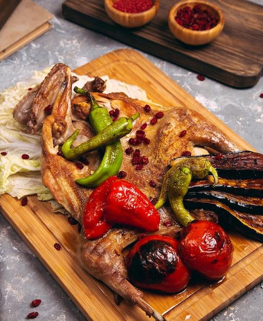 チェリートマト、木の板にピーマンとさまざまなバリエーションで鶏の胸肉グリル。 無料写真