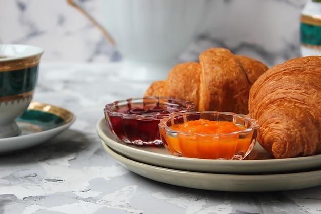 フランスの朝食、クロワッサン、アプリコットジャム、チェリージャム、紅茶、赤と黄色の花 無料写真