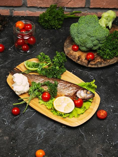 新鮮な魚のシーバスと料理の食材。スパイスと黒スレートテーブルの上のハーブ生魚シーバス。上面図。 無料写真