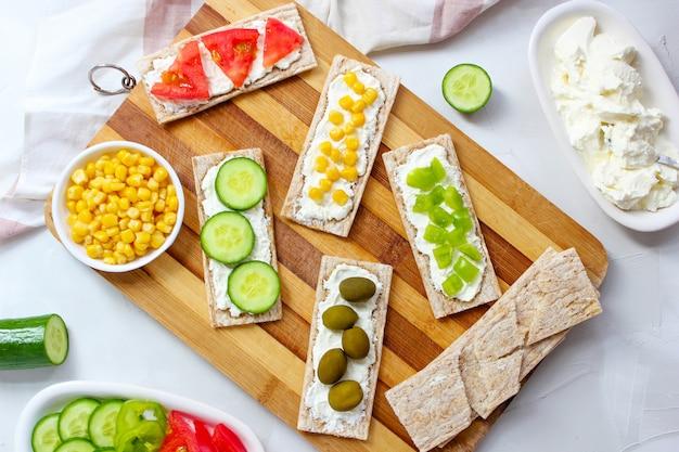 Домашние хрустящие хлебцы с творогом и зелеными оливками, кусочками капусты, помидорами, кукурузой, зеленым перцем на разделочной доске. концепция здорового питания, вид сверху. плоская планировка Бесплатные Фотографии