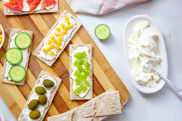 カッテージチーズとグリーンオリーブ、キャベツ、トマト、コーン、まな板の上のピーマンのスライスと自家製クリスプブレッドトースト。健康食品のコンセプト、トップビュー。フラットレイ 無料写真